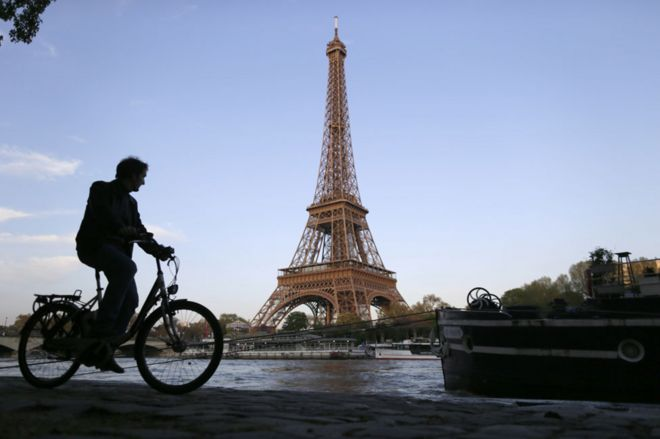 Cyclist on Seine towpath with the Eiffel tower in the background