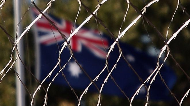 An Australian flag behind a wire fence