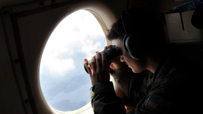 Search plane crew member uses binoculars to look through window of US patrol aircraft searching for missing EgyptAir flight. Sunday, May 22, 2016