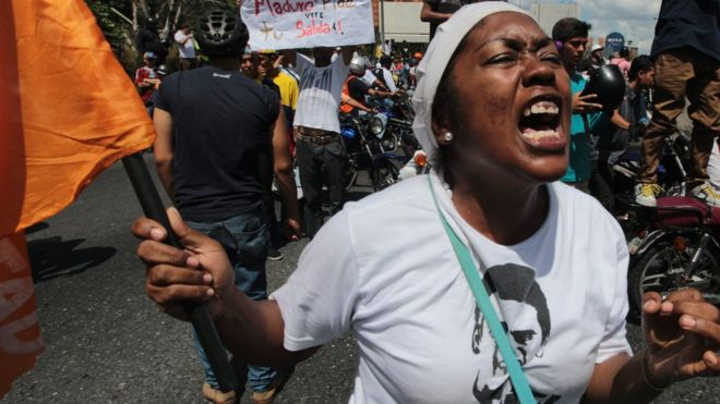 Una mujer protesta con una bandera