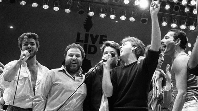 Michael (far left) joined the Live Aid finale at Wembley Stadium alongside (left-right) promoter Harvey Goldsmith, Bono, Paul McCartney, Bob Geldof and Freddie Mercury.