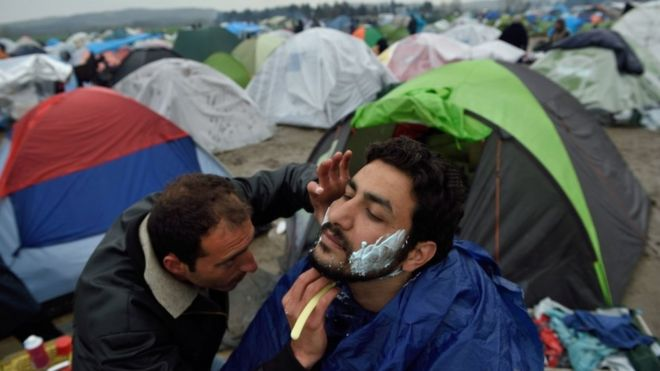 A migrant shaves another at a makeshift camp at the Greek-Macedonian border, near the Greek village of Idomeni