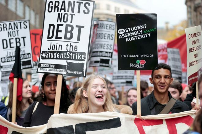Students hold placards, and banners at the protest in London