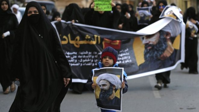 Bahraini protesters hold pictures of Sheikh Nimr al-Nimr in Daih, Bahrain, 3 Jan