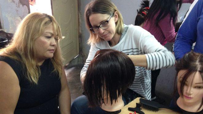 Carmita observa a Cassandra demostrar una técnica de corte de cabello