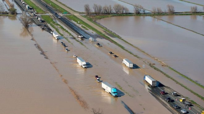 Vehicles trying to negotiate flooded Interstate 5 in Williams, north California, where more rain is expected