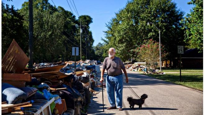 "Charles Tripp, of Rome, Georgia, walks Louie down his sister-in-law's street. He came down with family with an RV, supplies, and support. ""I am supervision, they're labor,"" he remarks pointing to family members, ""I just had heart surgery."" Denham Springs, LA."