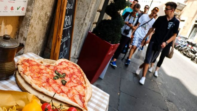Tourists walk past a heart-shaped pizza, in central Rome on 2 August 2016