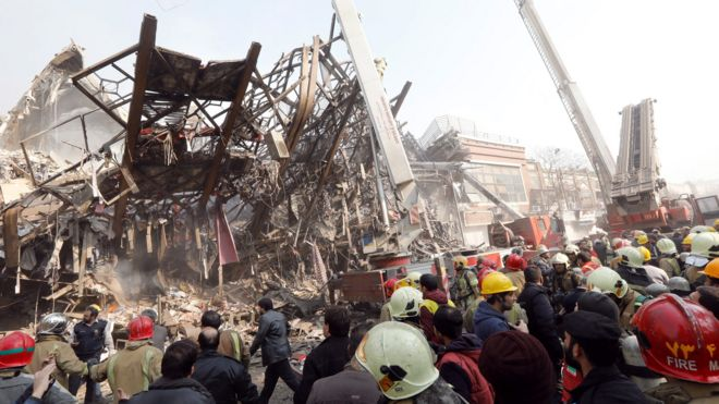Rescue workers gather in front of the collapsed Plasco building in Tehran, Iran (19 January 2017)