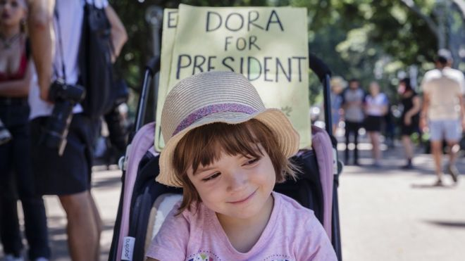 """A young child, before a sign saying """"Dora for President"""" attends an anti-U.S. President Donald Trump protest on January 21, 2017 in Sydney, Australia"""