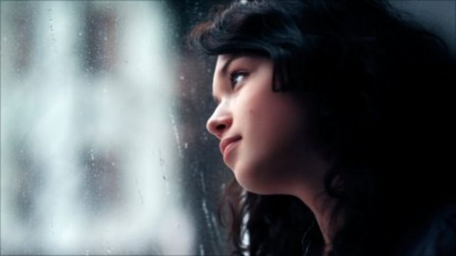 Woman gazing out of window