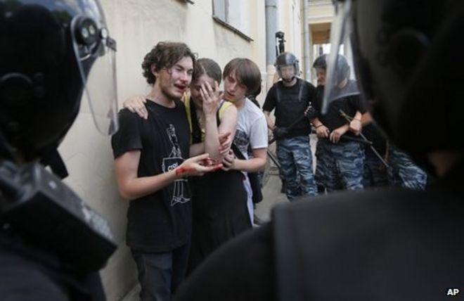 Russian police guard gay rights activists after they were attacked by rival protesters in St Petersburg BBC