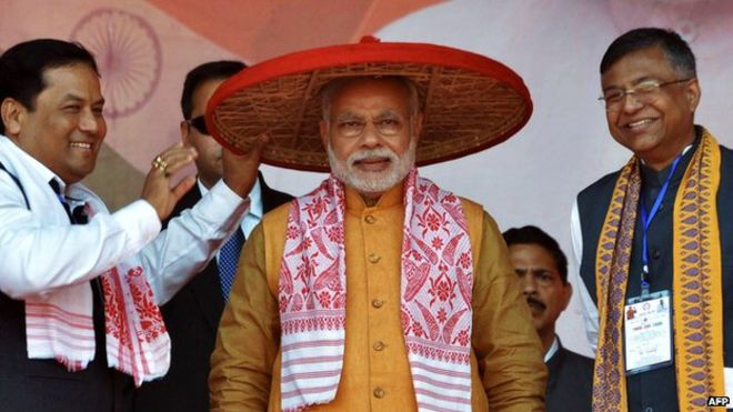 """Indian Prime Minister Narendra Modi is presented with a transitional Assamese hat known as a """"Japi"""" by Bharatiya Janata Party (BJP) leaders at a party rally in Guwahati on 30 November 2014."""