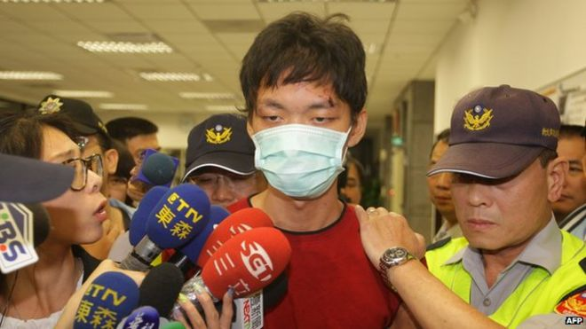 The alleged attacker Cheng Chieh (C) is transferred by policemen at a local police station in New Taipei City on 22 May 2014.