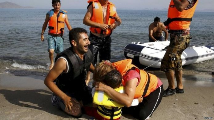 Iranian migrant cries next to his son and wife moments after arriving on a Kos beach in a small, exhausted group that paddled a dinghy from Turkey 15/08/2015