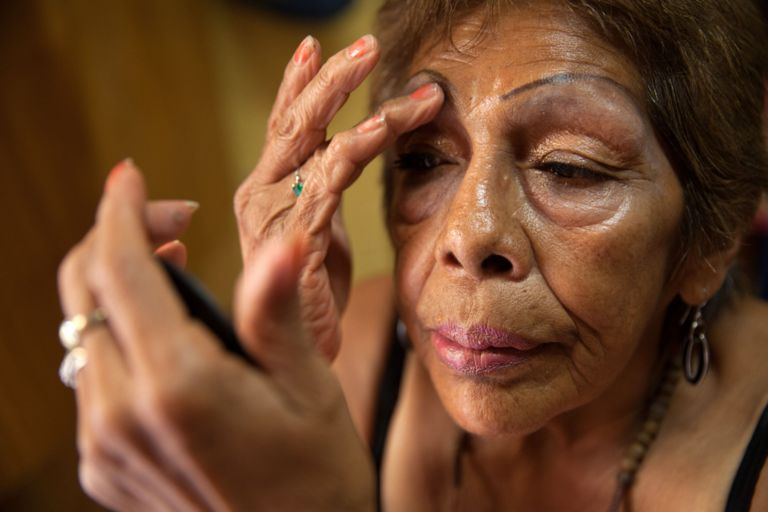 Luchita, a resident of Casa Xochiquetzal, puts on make-up in her bedroom at the shelter