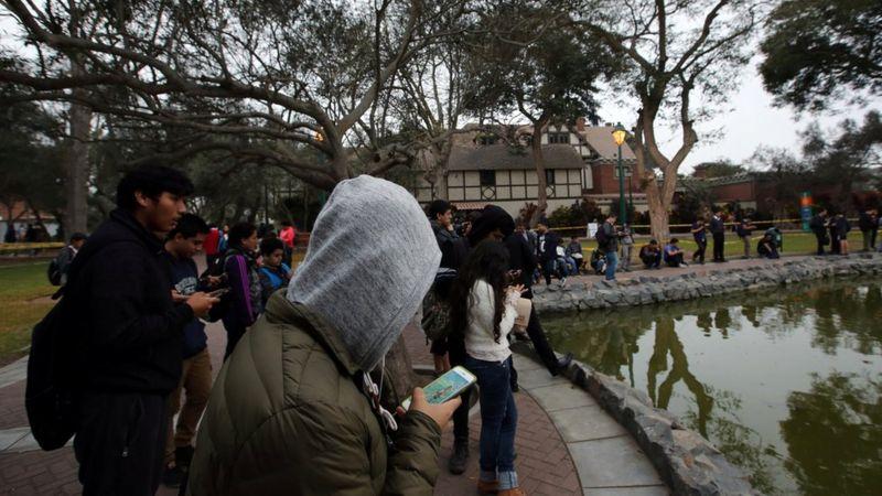Jovens diante de uma lagoa olhando os celulares