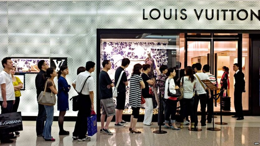 File photo: Shoppers queue to enter a shop of French luxury brand Louis Vuitton in a shopping mall in Shanghai, 14 June 2010