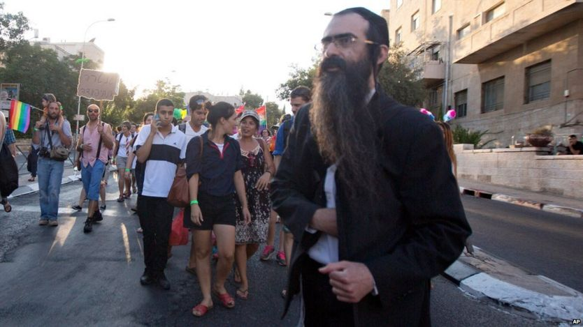 Ultra-Orthodox Jew Yishai Schlissel walks through a Gay Pride parade and is just about to pull a knife from under his coat and start stabbing people in Jerusalem, Thursday, July 30, 2015.