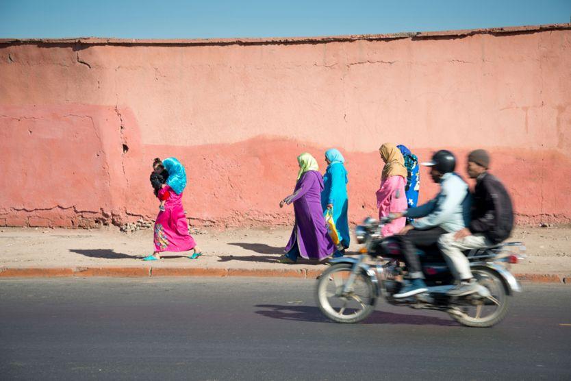 Men on motorbike pass women walking - Marrakech