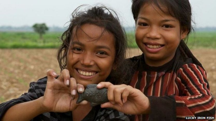 Children holding an iron fish in Cambodia