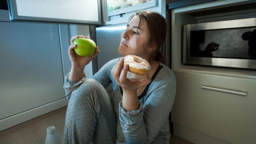 Mujer pensando en si comer una manzana o una dona