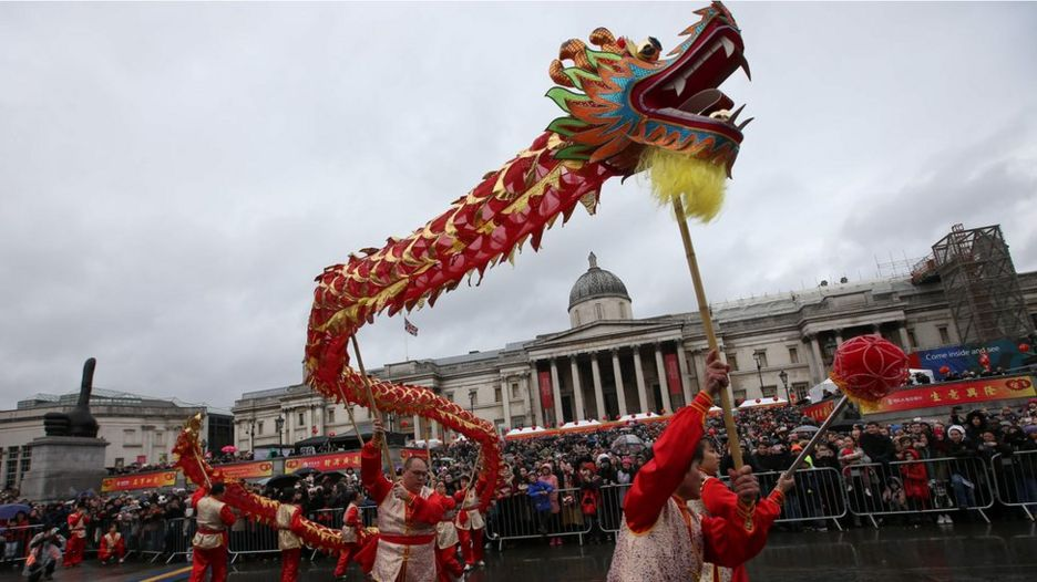 "Members of the Chinese community perform a ""dragon dance"" in a front of a crowd backed by the National Gallery"