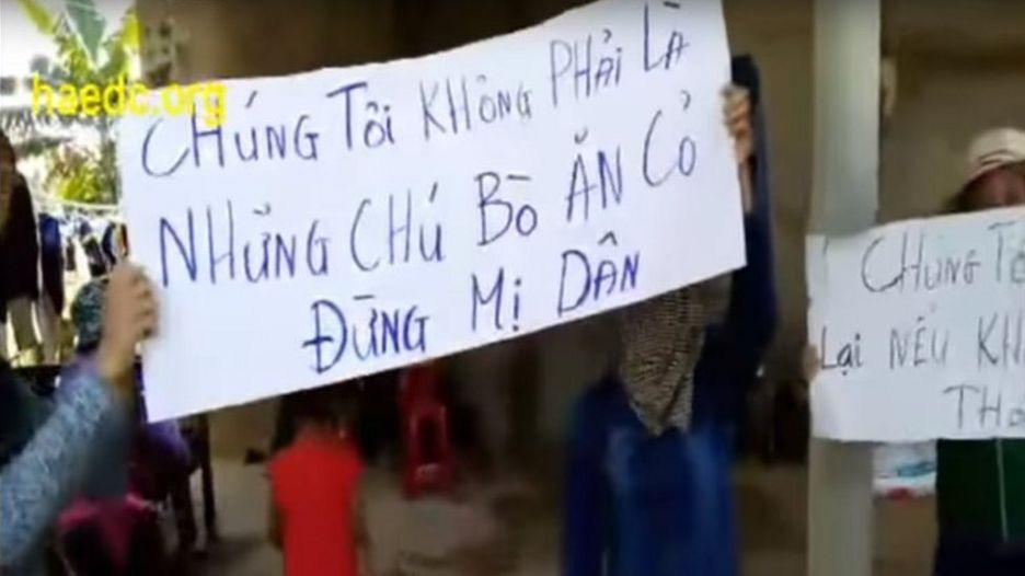 Người biểu tình giơ cao biểu ngữ trước cửa nhà trưởng thôn Cồn Sẻ