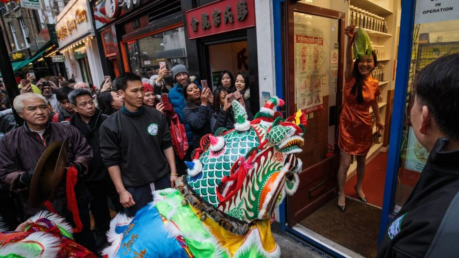 Performers in costume receive offerings from local businesses in Chinatown during the Chinese New Year celebrations