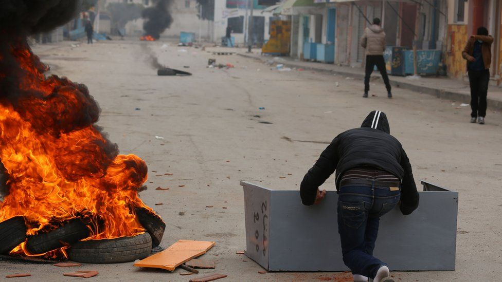 Tunisian boys throw stones towards a police station in a town at the border with Libya