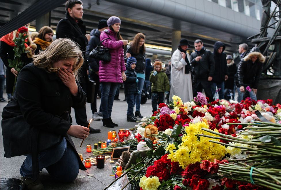 A woman holds a candle at a memorial for the victims of downed Airbus A321, at the Pulkovo Airport on November 1, 2015 in St. Petersburg, Russia.