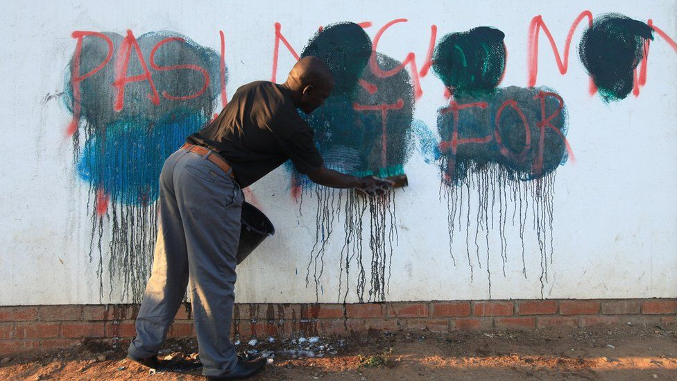 A man trying to srub off anti-government graffiti from a wall in Harare, Zimbabwe - Tuesday 6 September 2016