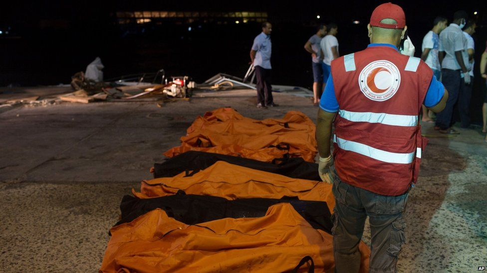 Rescuers gather around the bodies of drowned migrants in Zuwara, Libya (27 August 2015)