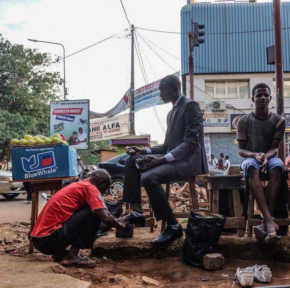 Maliyyə işçisi küçədə çəkmələrini parıldadır