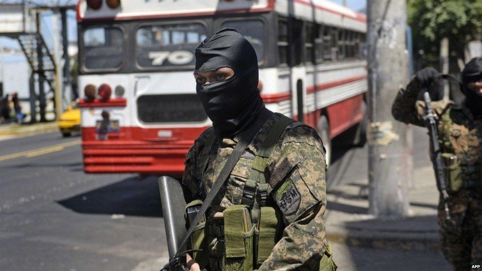Soldiers guard El Salvador buses...