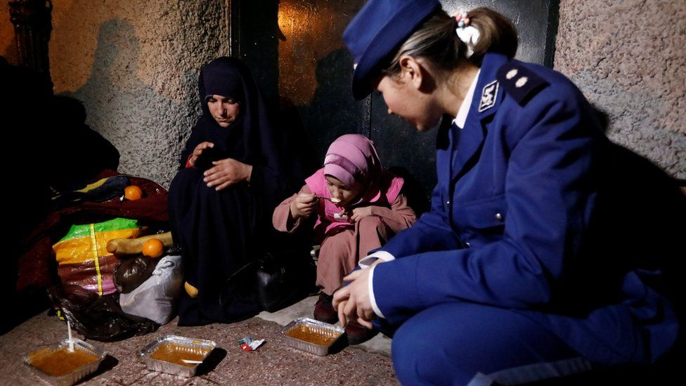 A police lieutenant kneels as she watches a homeless girl eat