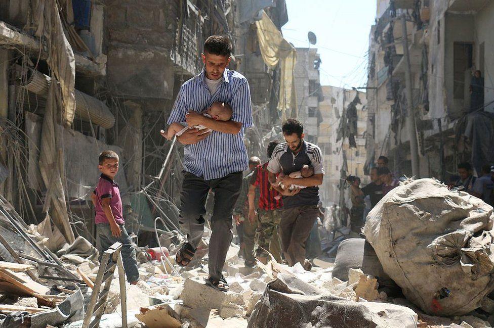 Hombres sirios cargando bebés entre los escombros de edificios en Alepo, 11 de septiembre de 2016.