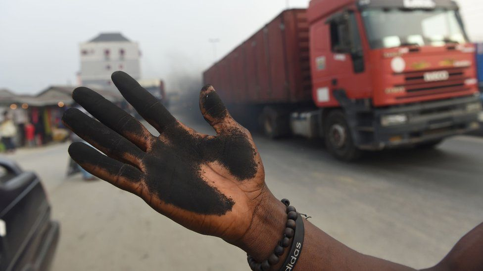 A man holds out his soot covered hand that he used to illustrate how much soot covered the bonnet of his car.