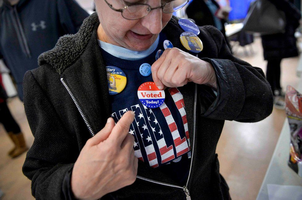 """A voter puts on an """"I voted"""" sticker"""
