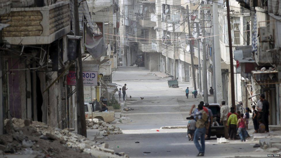 People walk in a street in the north-western city of Ariha, after a coalition of insurgent groups seized the area in Idlib province