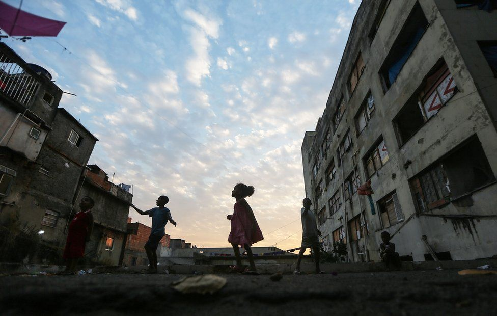 Youngsters fly kids outside an occupied building in the Mangueira'favela' community on 9 August, 2016