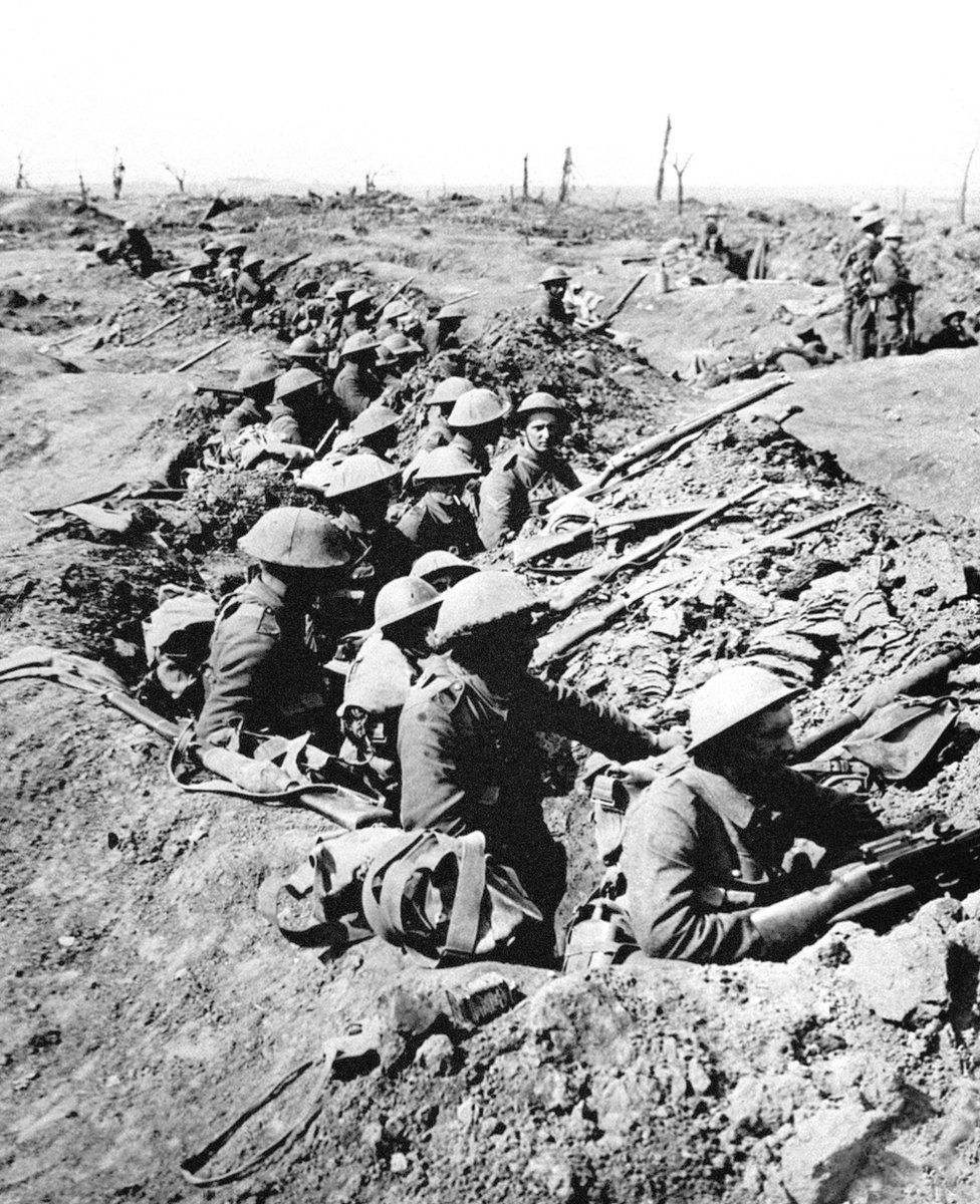 British infantrymen occupy a shallow trench in a ruined landscape before an advance during the Battle of the Somme