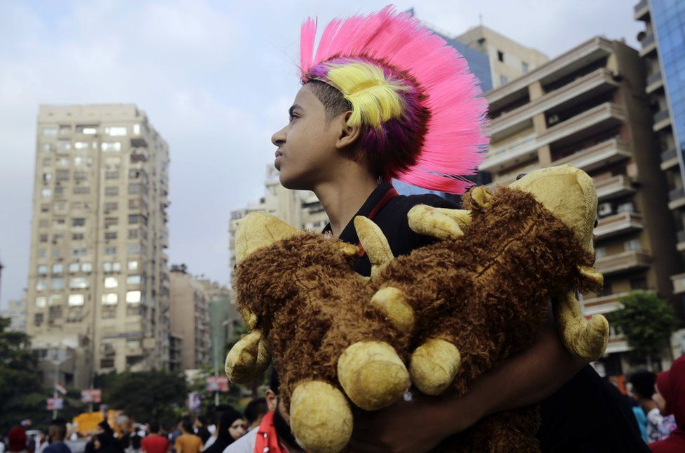 A boys sells stuffed animals after the dawn Eid al-Adha prayers at Moustafa Mahmoud Square in Cairo, Egypt - Monday 12 September 2016