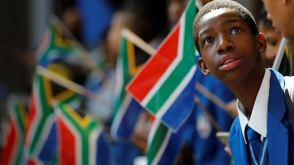 A school boy stands with others holding South African flags, OR Tambo International Airport, Johannesburg, South Africa - Wednesday 7 September 2016