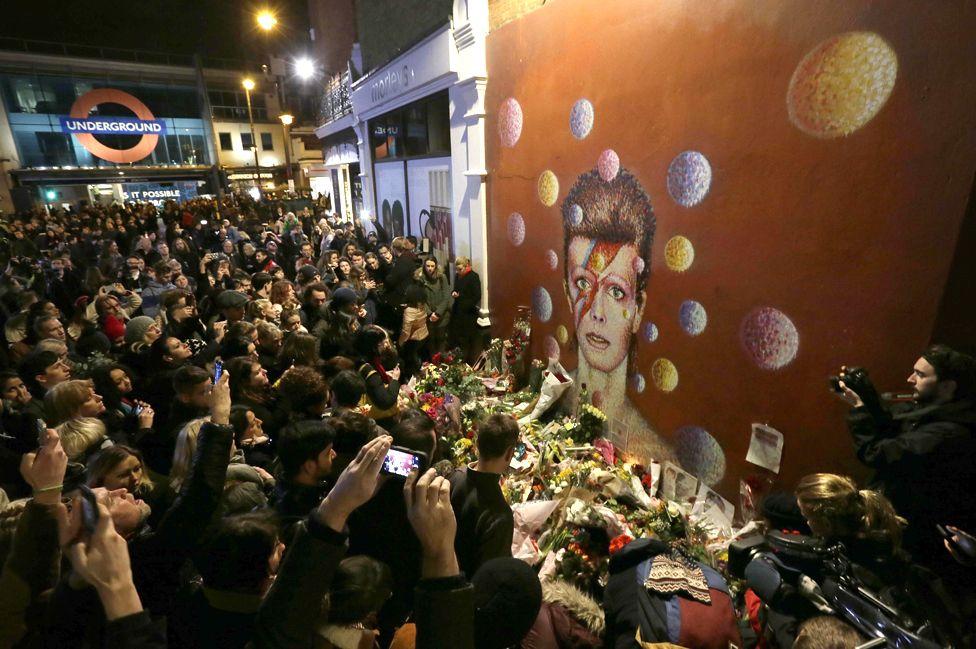 Una multitud frente al mural del cantante David Bowie hecho por el artista Jimmy C, en Brixton, Londres.