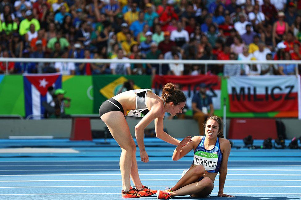 Abbey D'Agostino wa United States (kulia)akisaidiwa na Nikki Hamblin wa New Zealandbaada ya kuanguka katika mbio za mita 5,000m- wanawaketarehe 16 Agosti 2016 mjini Rio de Janeiro, Brazil.