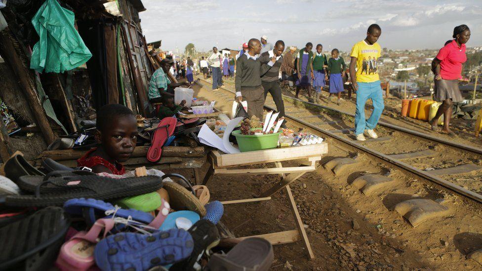 Students walking along a railway track with stall alongside in Kibera, Nairobi, Kenya - Tuesday 7 February 2017
