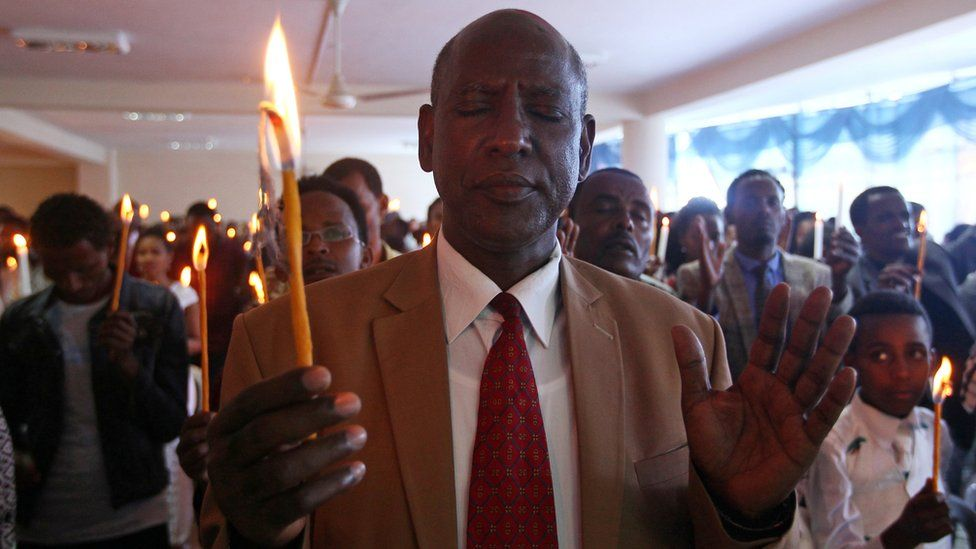 """A man attends a prayer session during a candle and prayer ceremony for the demonstrators killed in the recent Oromo protest, in Ethiopia""""s capital Addis Ababa, September 11, 2016"""