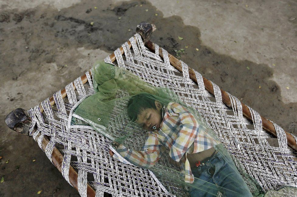 A boy covered with a mosquito net sleeps in a cot on a hot summer day in New Delhi, India