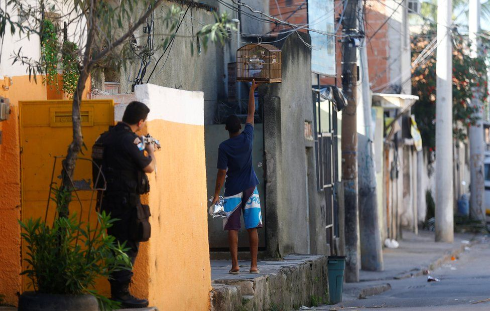A policeman aims his weapon as a resident holds a bird cage during an operation against drug dealers in Cidade de Deus or City of God slum in Rio de Janeiro